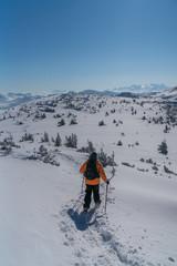 Mann mit Schneeschuhen geht auf den Berg Gipfel
