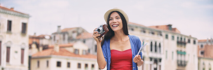 Wall Mural - Travel tourist woman photographer holding vintage camera in Venice, Italy. Asian girl on summer holiday banner. Mixed race Asian Caucasian model in her 20s traveling in Europe.