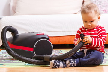 Little baby boy playing with pipe of vacuum cleaner with brush