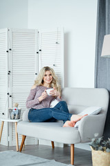 Young blonde beautiful lady drinking tea at home
