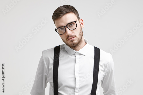 7464abb4bc2e Serious handsome young unshaven male employee wearing trendy eyeglasses and  white formal shirt with suspenders posing isolated against white studio  wall ...