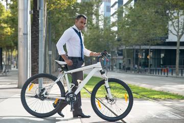 Businessman walking with bicycle on urban street