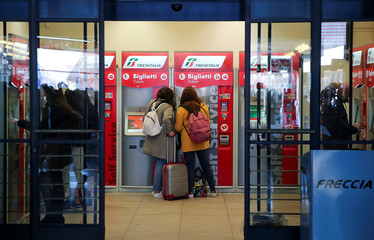 Passengers buy train ticket at the Trenitalia self-service ticket machine at the Santa Lucia Station in Florence