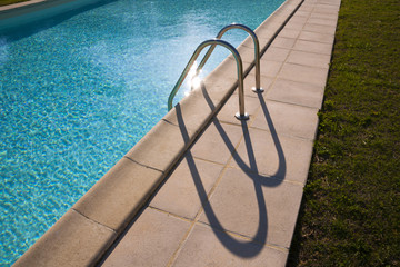 Graphic semi-abstract shape of outdoor swimming pool ladder shadows