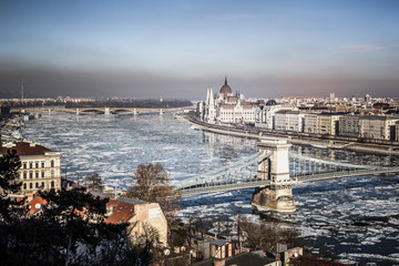 Panorama of Budapest - Parliament, chain bridge, river Danube in the spring with ice drifts, Budapest, Hungary