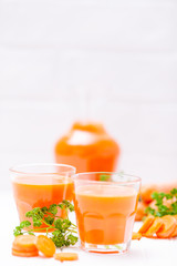Carrot juice in beautiful glasses, cut orange vegetables and green parsley on white wooden background. Fresh orange drink. Close up photography. Selective focus. Vertical banner