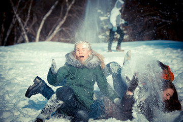 Girls in winter.  young girl is having fun in a winter park with friends. Active rest in winter. students playing with snow. girls fall in the snow and laugh