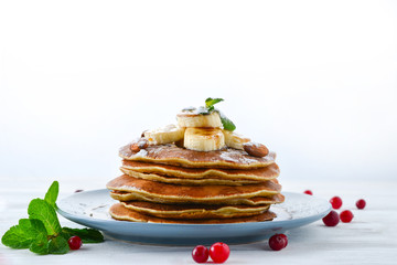 Pancakes with caramel, banana and nuts decorated with cranberries and mint with juice.