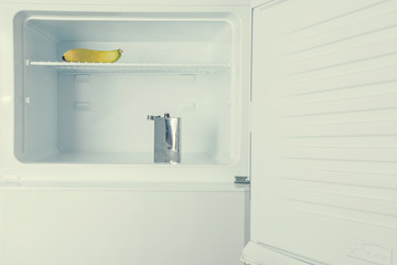Abstract photo of a yellow banana and metal flask inside the refrigerator