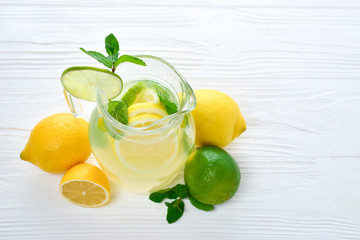 Citrus lemonade and lime water with lemon sliced , healthy and detox water drink in summer on white wooden table