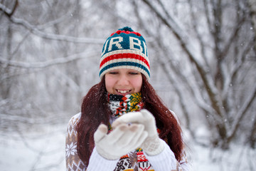 Photo of smiling woman in knitted cap and scarf catching snowflakes in winter forest during day