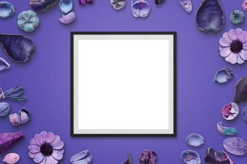 Picture frame on purple desk with flower decorations. Isolated frame for picture or text mockup. Top view.