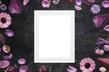 Picture frame on black wooden desk surrounded with purple floral decorations.