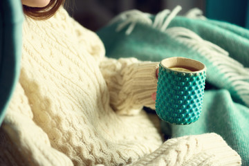 Woman's hand in woolen sweater holding cup of tea with lemon on a cold day. Copy space. Winter and Christmas holidays concept.