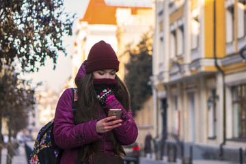 Pretty Brunette Girl Wearing Purple Winter Coat, Hat and Scarf, Walking by European Street at Winter, Using Her Smartphone and Making Selfie