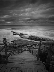 Beautiful rocky beach in the Portuguese coastline in a stormy day. Seascape. Long exposure.