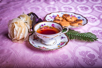 Old antique cup of tea on pink table cloth