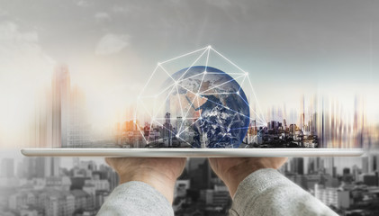 Hand holding digital tablet with global network connection technology and modern buildings. Element of this image are furnished by NASA