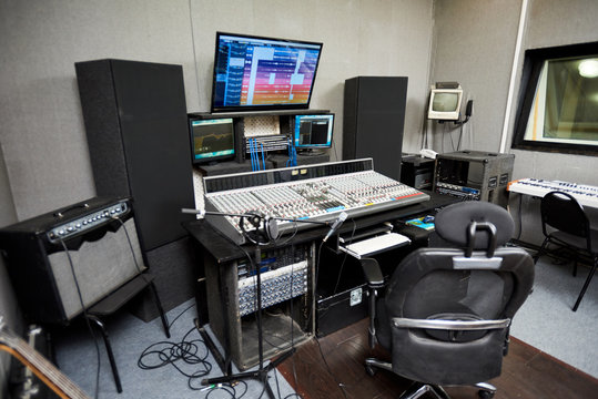 Modern audio workstation equipped with computer, microphone on stand, control surface and loudspeakers