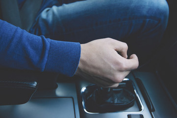 Man's hand on the gear shifter in the  fast sport car