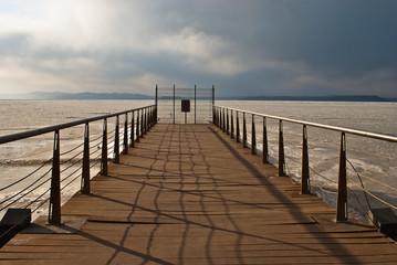 Pier. Wooden bridge. The frozen sea.