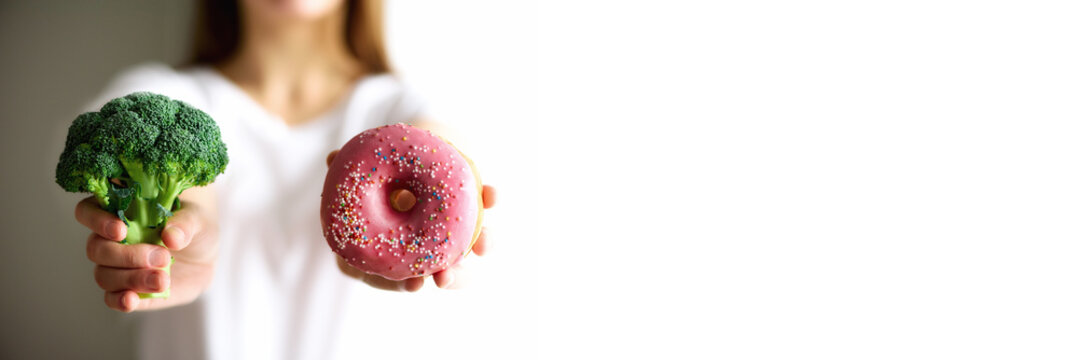 Young woman in white T-shirt choosing between broccoli or junk food, donut. Healthy clean detox eating concept. Vegetarian, vegan, raw concept. Copy space. Banner