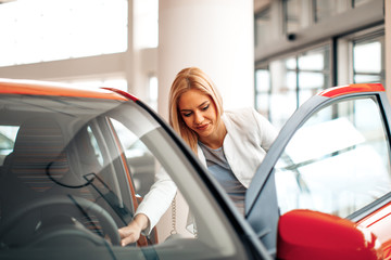 Young woman choosing new car for buying in dealership shop