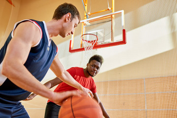 Concentrated confident young African-American man controlling basketball competitor dribbling trying to score point on court