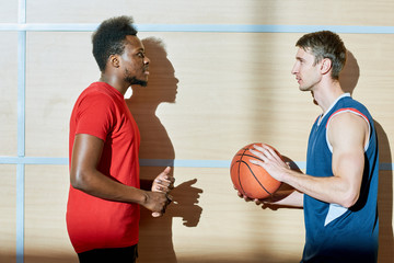 Serious handsome young interracial friends talking about basketball while discussing plan of game and thinking of technique in gym