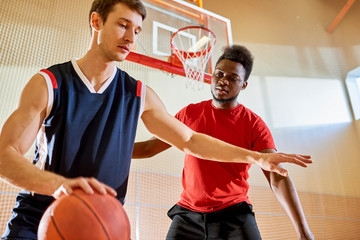 Sporty handsome young multiethnic athletes playing basketball on court: concentrated Caucasian man protecting ball from competitor while dribbling