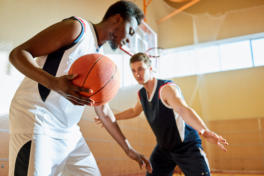 Concentrated sporty young African-American basketball player moving with ball on court while his opponent blocking way to protect basket
