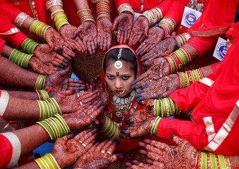 Brides display their hands decorated with henna around a bride as she poses for her own photographer during a mass marriage ceremony in which, according to its organizers, 70 Muslim couples took their wedding vows, in Ahmedabad