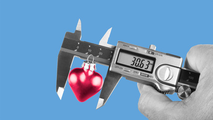 Black and white human hand holding a caliper when measuring a red heart. Idea for the size of love or its relation to science or technology. Isolated on sky-blue background.