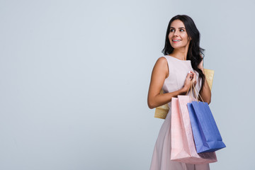 In love with shopping. Beautiful young woman holding shopping bags and looking away with smile while standing against white background