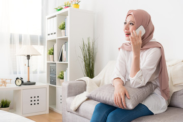 cheerful muslim woman sitting on sofa relaxing