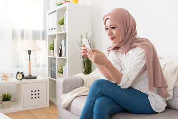 smiling attractive muslim lady sitting on sofa