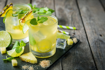 In de dag Cocktail Pineapple and lime drink on rustic background