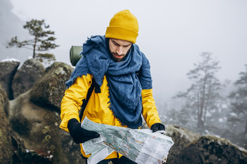 Tourist in yellow clothes reads a map standing on the rock enveloped in fog