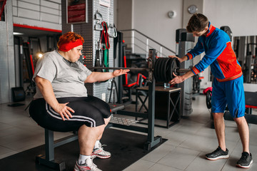 Fat woman using barbell, training with instructor