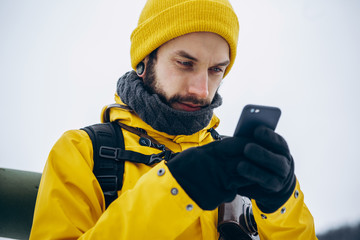 Tourist in yellow suit checks something in his smartphone walking around the mountains covered with snow