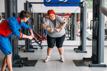 Fat woman training with instructor, hard workout