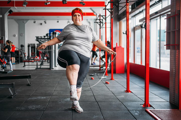 Fat sweaty woman doing exercise with rope in gym