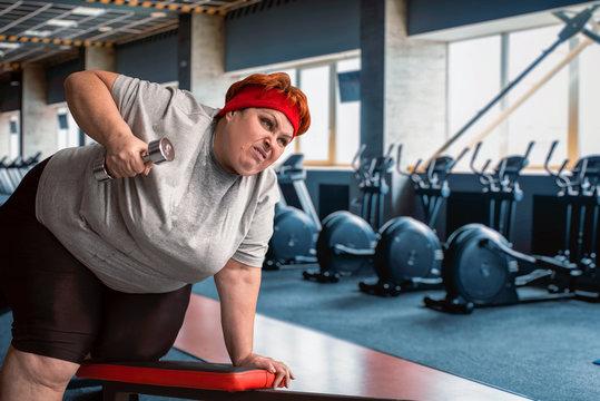 Fat sweaty woman using dumbbells in gym