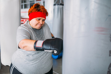 Fat woman in boxing gloves works with punching bag