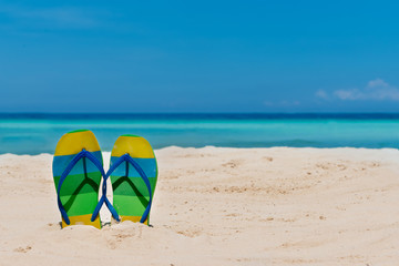 sandal flipflops on a sandy ocean beach with blue sea and blue background