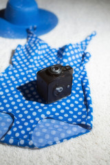 Blue vintage hat with swimsuit and camera displayed on white carpet floor.