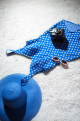 Blue vintage hat with swimsuit, camera and sunglasses displayed on white carpet floor. Top view.