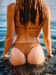 Wet attractive woman with perfect body standing up in sea, wearing stylish bikini.