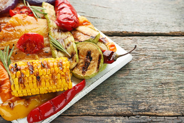 Grilled vegetable on white cutting board with rosemary