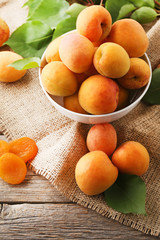 Sweet apricots in bowl on grey wooden table